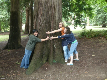 girls hugging tree