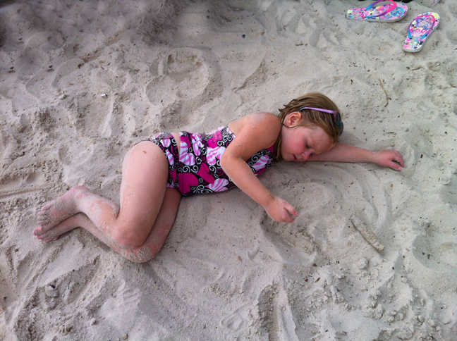 Young girl plays in sand