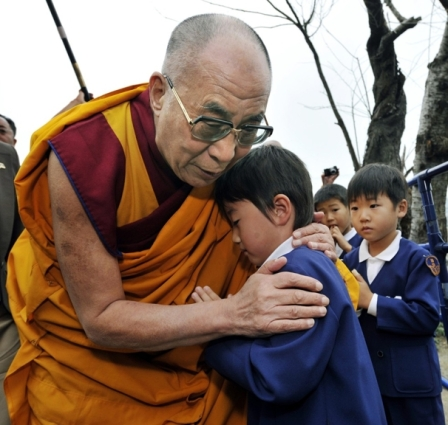 Dalai Lama hugs young boy